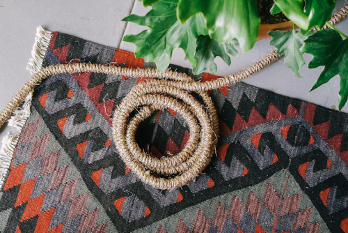 A loop of rope-wrapped cable on a rug.