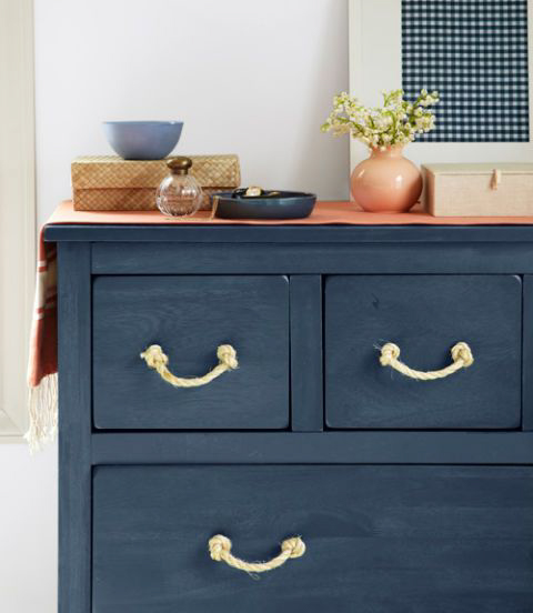 A navy blue chest of drawers with rope handles.