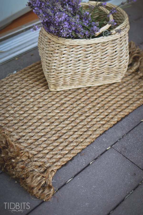 A rope door mat with a basket of purple flowers on top.