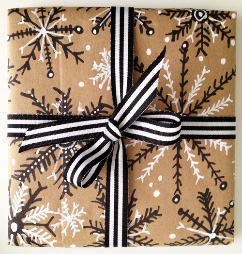 A gift wrapped in brown paper decorated with pen.