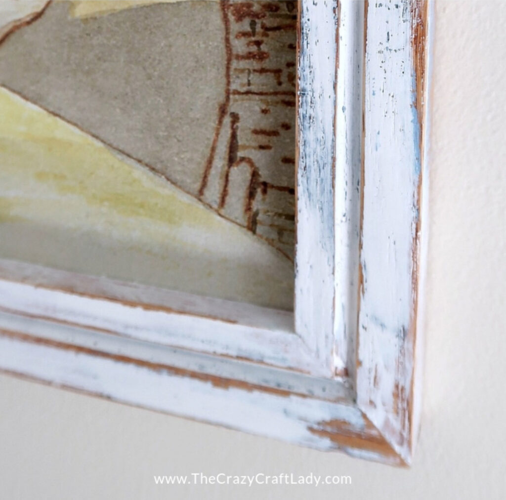 A rustic distressed painted picture frame.