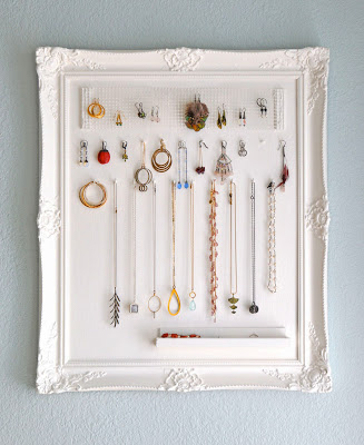 Necklaces and earrings hanging inside a white frame.