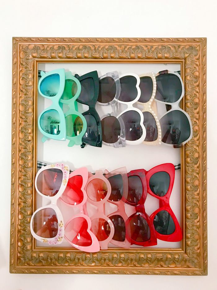 Rows of sunglasses hanging inside a picture frame.
