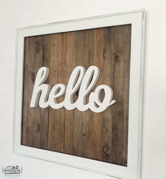 A sign saying hello on a wooden background.