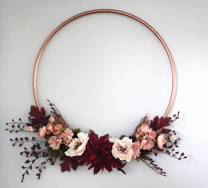 A copper hula hoop decorated with red autumn flowers.