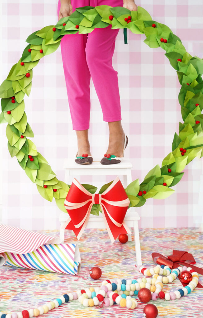 A lady in pink trousers holding an oversized Christmas wreath.