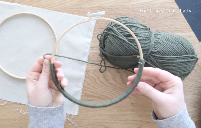 wrap half the embroidery hoop with green yarn