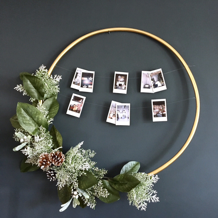 A gold hoop decorated with Christmas greenery.