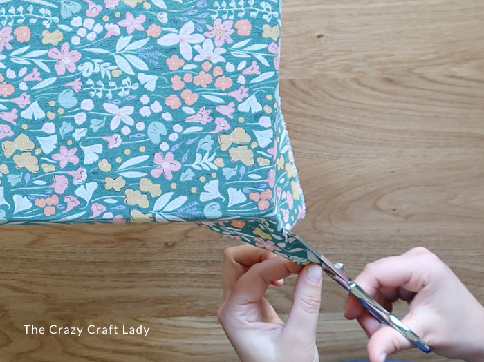Cut out a small triangle from each corner of the fabric
