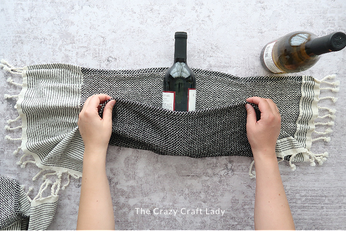 Fold the lower third of the towel up over the wine bottle