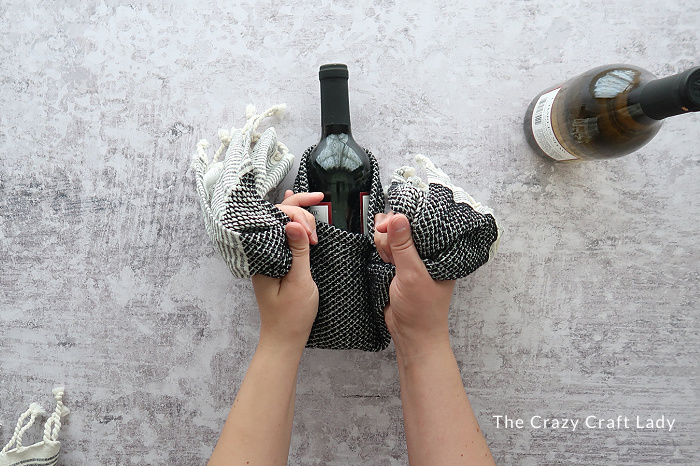 Tie the two towel ends in a knot in the center of the bottle