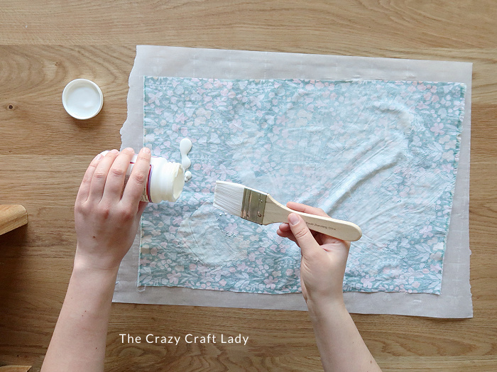 apply a generous coat of Mod Podge to the back of the fabric with a paintbrush