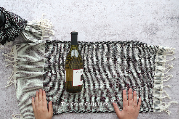 lay the towel flat - place the wine bottle on top