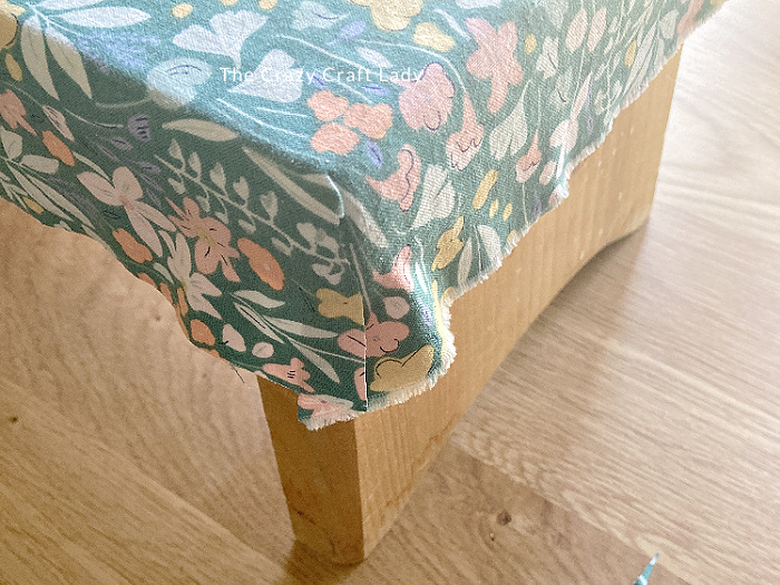 smooth the cut fabric corners over the rounded edge of the wood stool