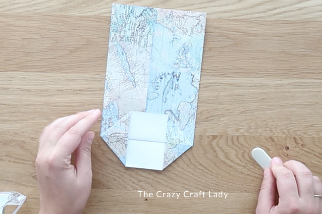 Separate the two bottom paper edges and fold in the corners to create triangles