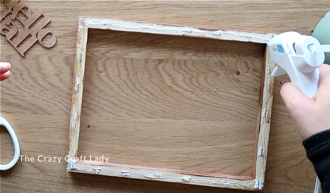 add hot glue around the back of the wood frame