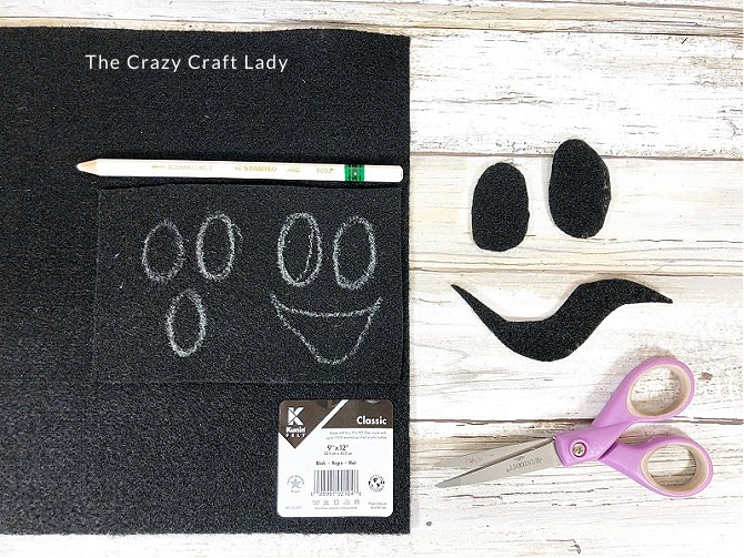 cut out black ghost faces from black felt