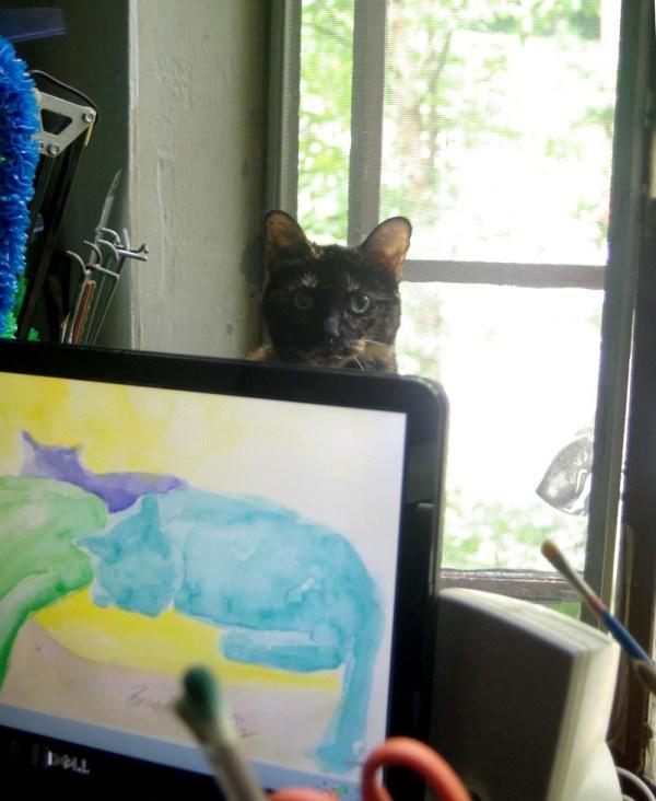 tortoiseshell cat behind computer