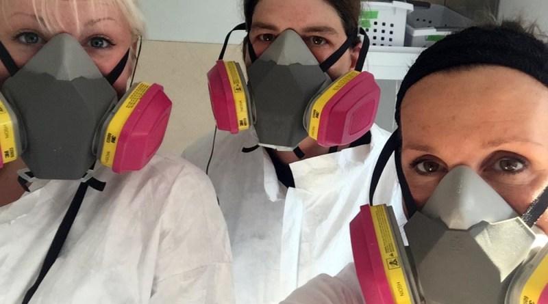 Sydney Bader, Meghan DeStefano and Margo Cicci Wisniewski don hazmat suits and respirator masks.