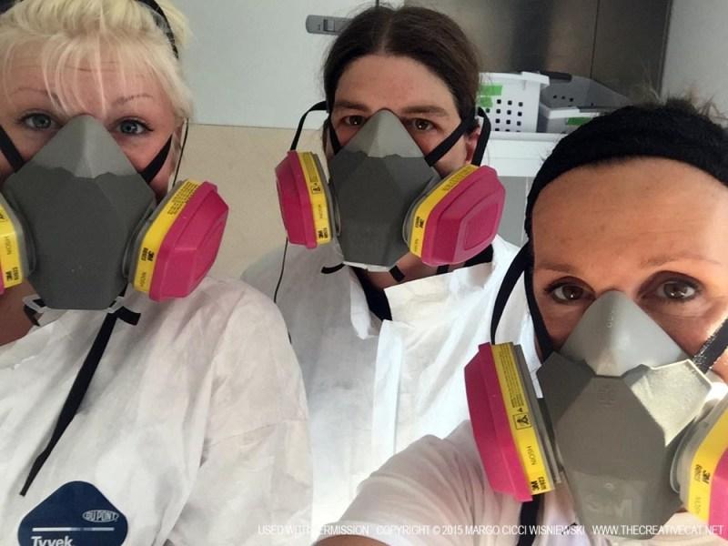 Sydney Bader, Lisa Kalmeyer and Margo Cicci Wisniewski don hazmat suits and respirator masks.