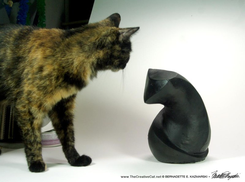 Kelly, acting as studio assistant, cautiously approaches the sculpture.