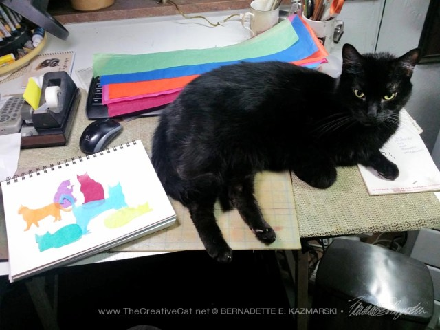 black cat on drafting table with artwork