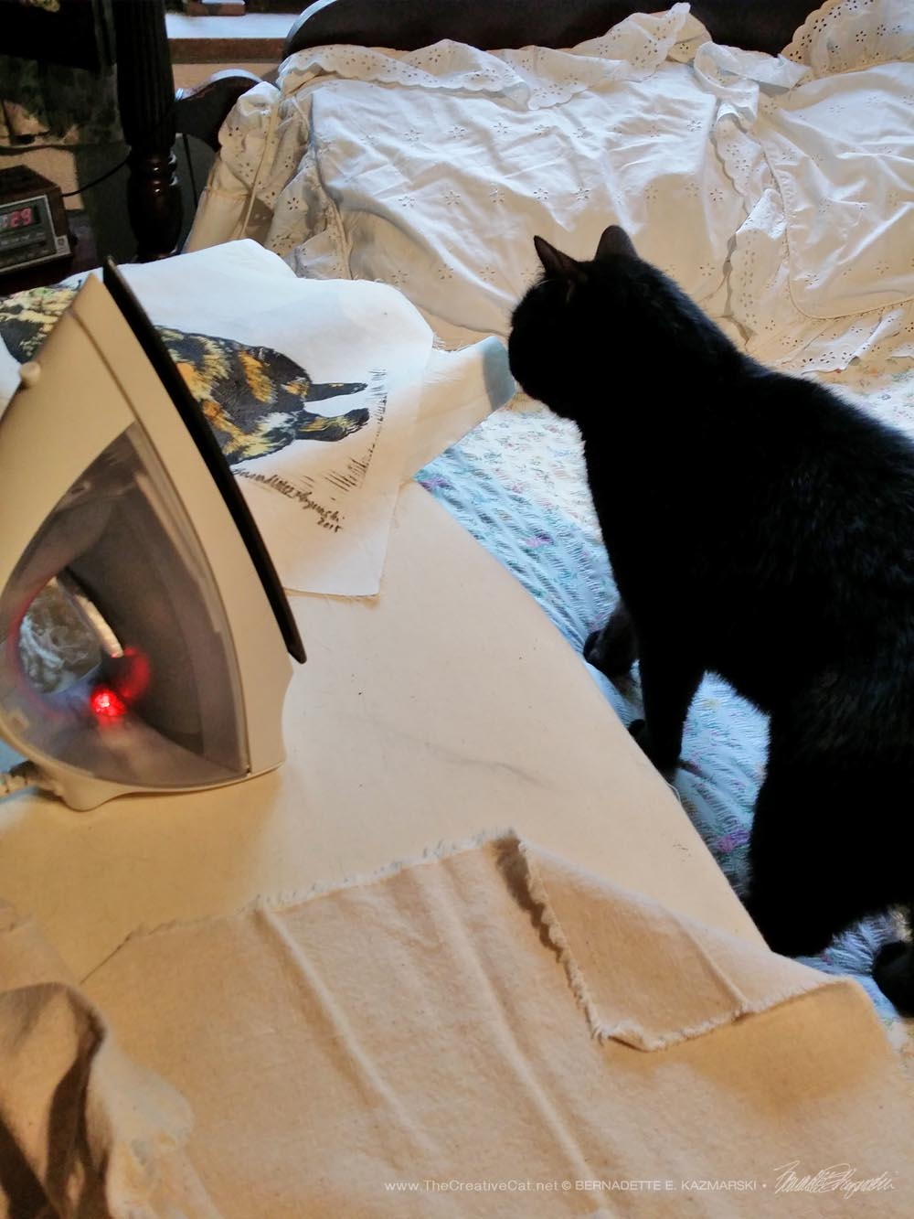 Mewsette inspects my materials as I iron the designs on the bags.