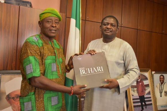 Adesina presenting a compedium of President Buhari's achievements to Ogunfeyitimi
