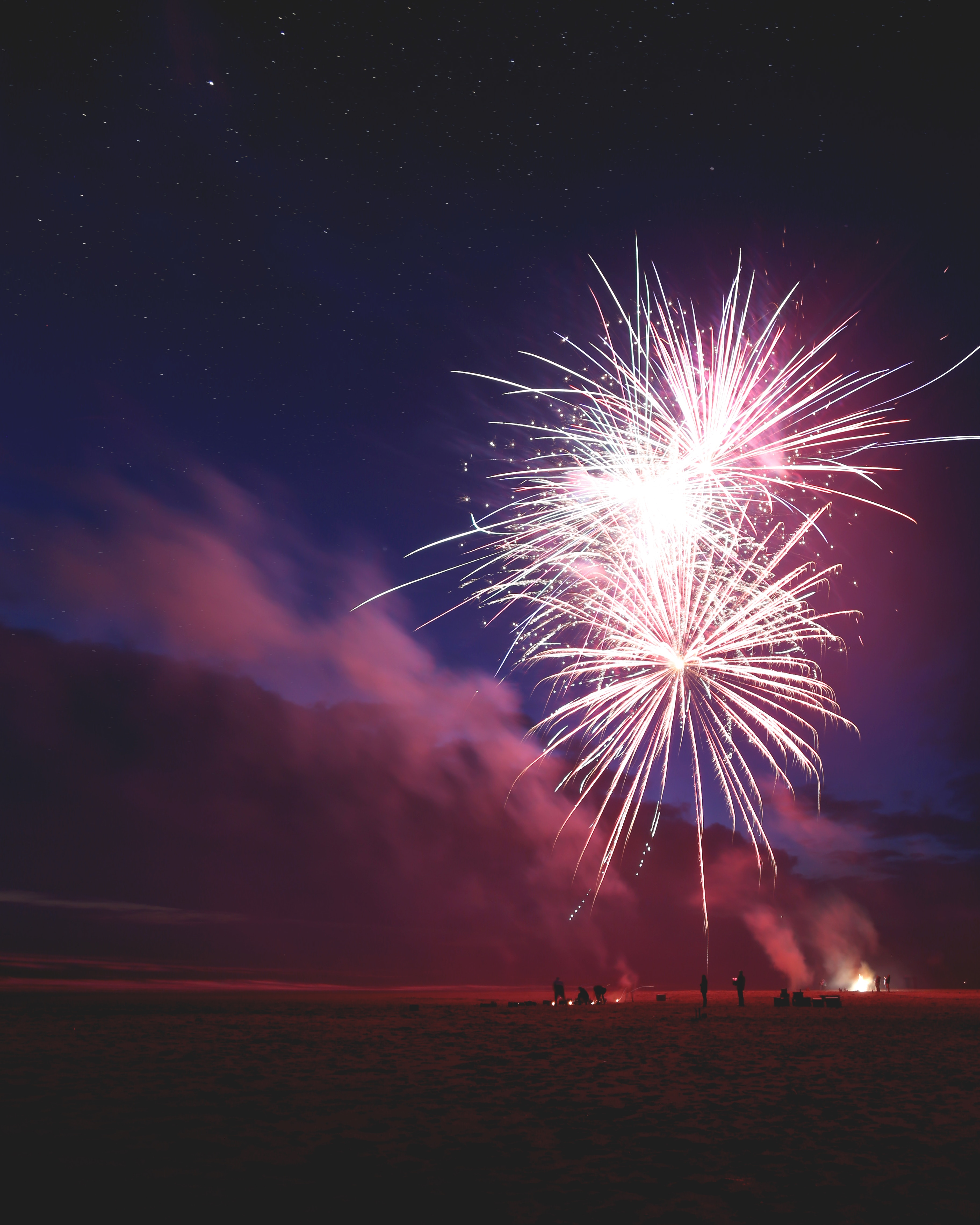Fireworks in a dark sky with people standing nearby watching. Photo by Jordan Steranka on Unsplash