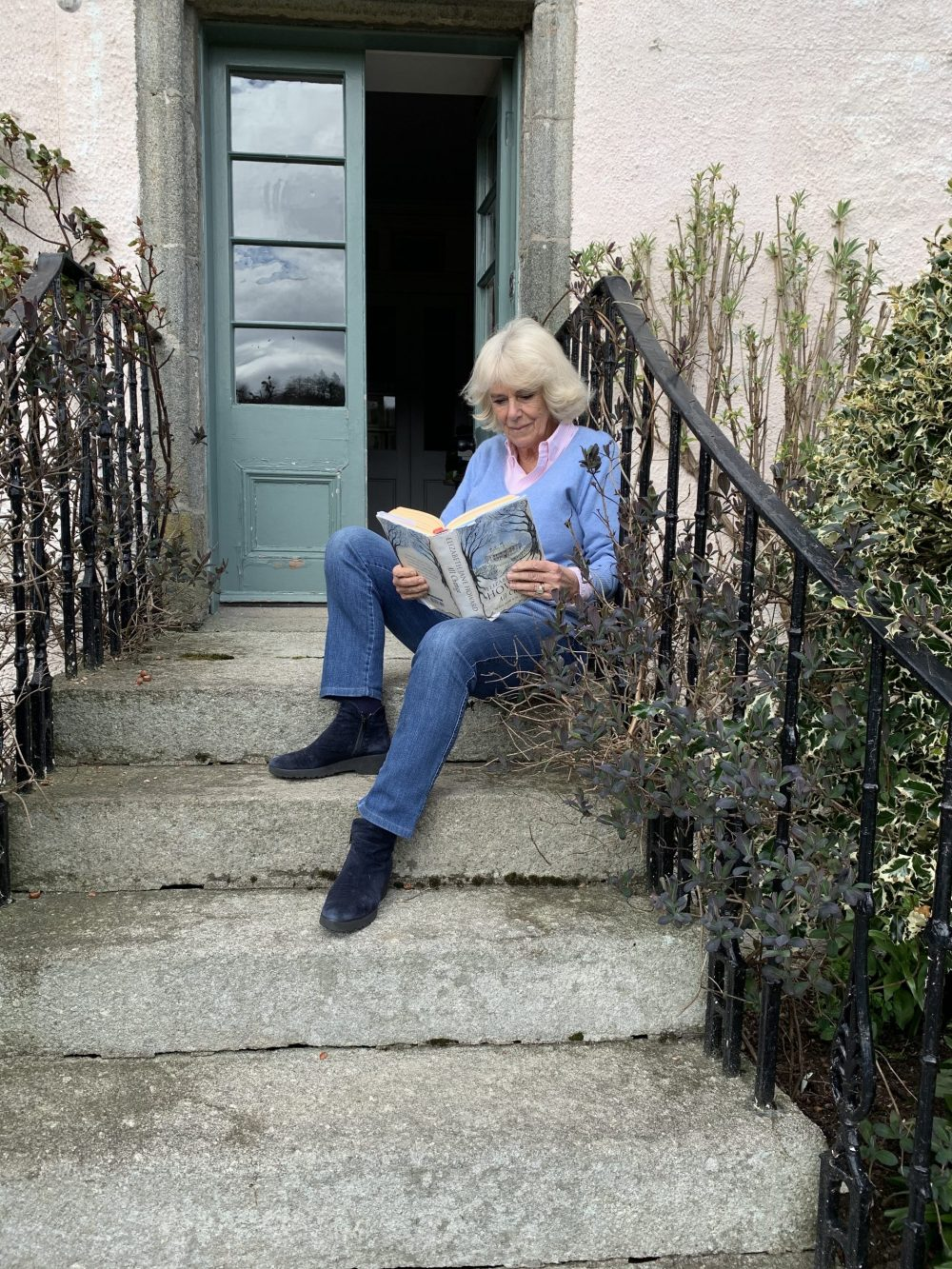 The Duchess of Cornwall reads 'All Change' - part of The Cazalet Chronicles - on a step at Birkhall (Clarence House)