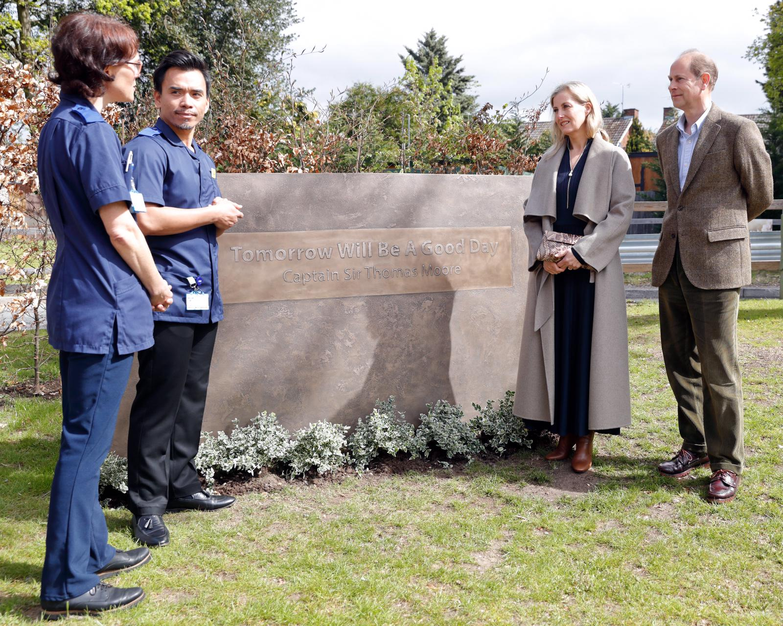 the earl and countess of wessex stand next to a stone plinth reading 'tomorrow will be a good day', the saying of captain tom moore. edward and sophie stand on the right, wearing a tweed jacket and grey long coat respectively, as they chat to two nurses in uniform