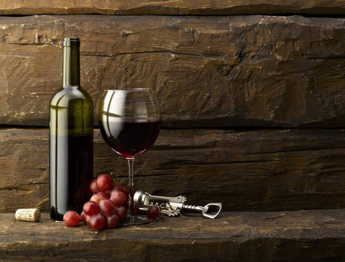 red wine with grapes on a wood background