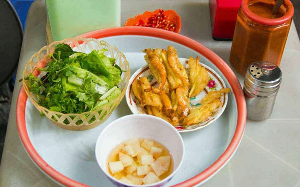 Plate of Banh Tom, battered and deep-fried shrimp,a popular Vietnamese street food. Served in a white platter with a bright orange room with a bowl of lettuce and dipping sauce.