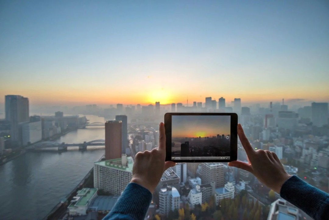 Girl taking picture of Tokyo with tablet