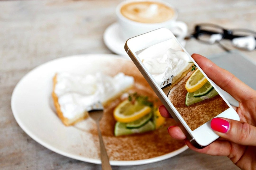Woman taking photo of dessert with iPhone