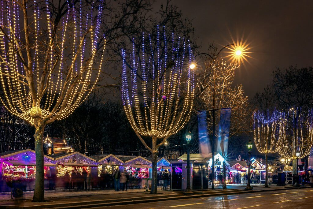 Festively decorated and illuminated Champs Elysees and Christmas market at night, France