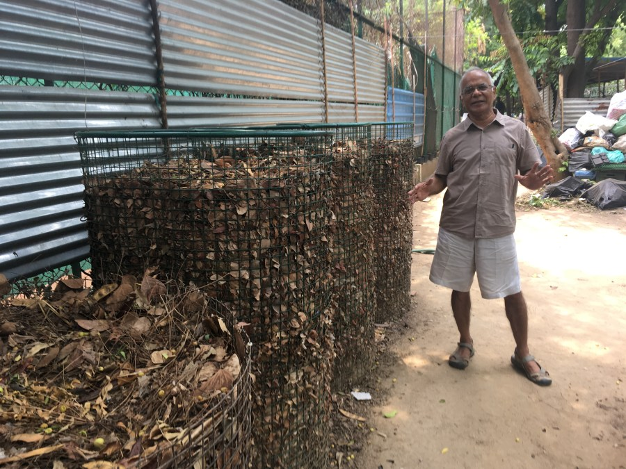 Keshav uncle dressed in shorts and standing next to a pile of leaves.