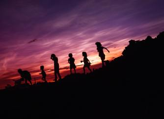 Children jumping and running in a sunset.