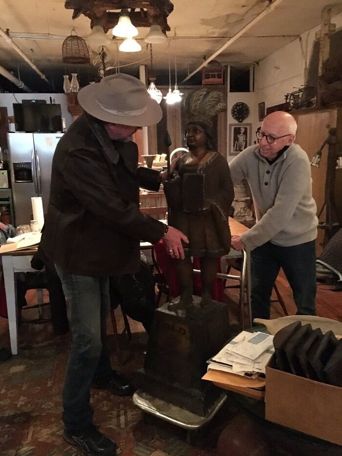 Will Evans and Allan Katz moving a Cigar Store Indian