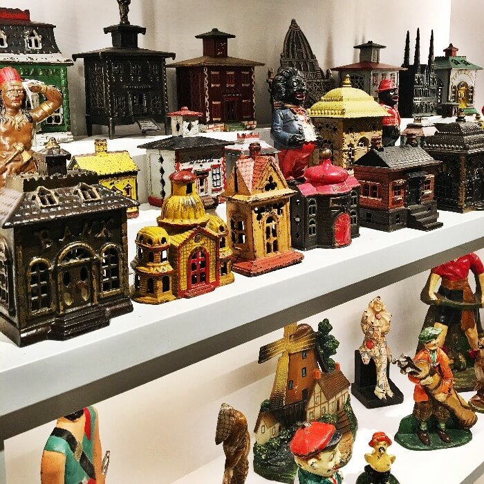 a row of colored metal antique Toy Banks at the Winter Antiques Show