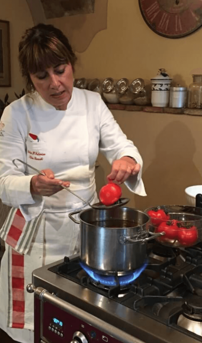 Female Chef Sylvia Baracchi in a white coat lifting a red tomato from a silver pit