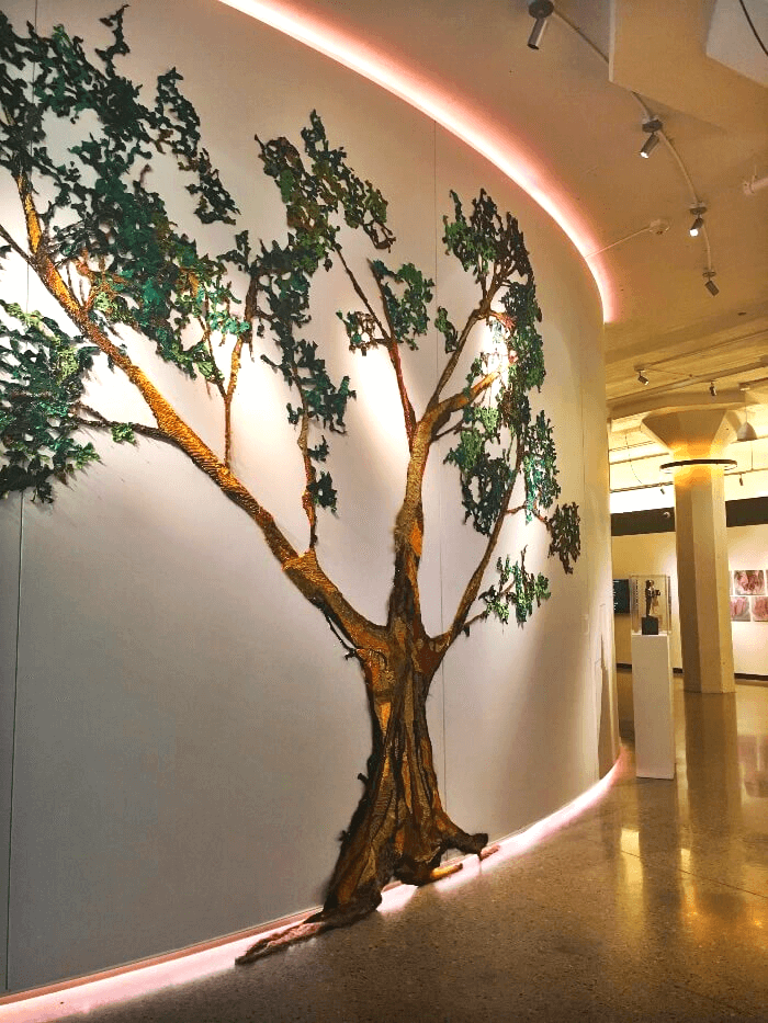 Neon pink lights and a tree painted on a wall decorate the 21c Oklahoma City Hotel Lobby