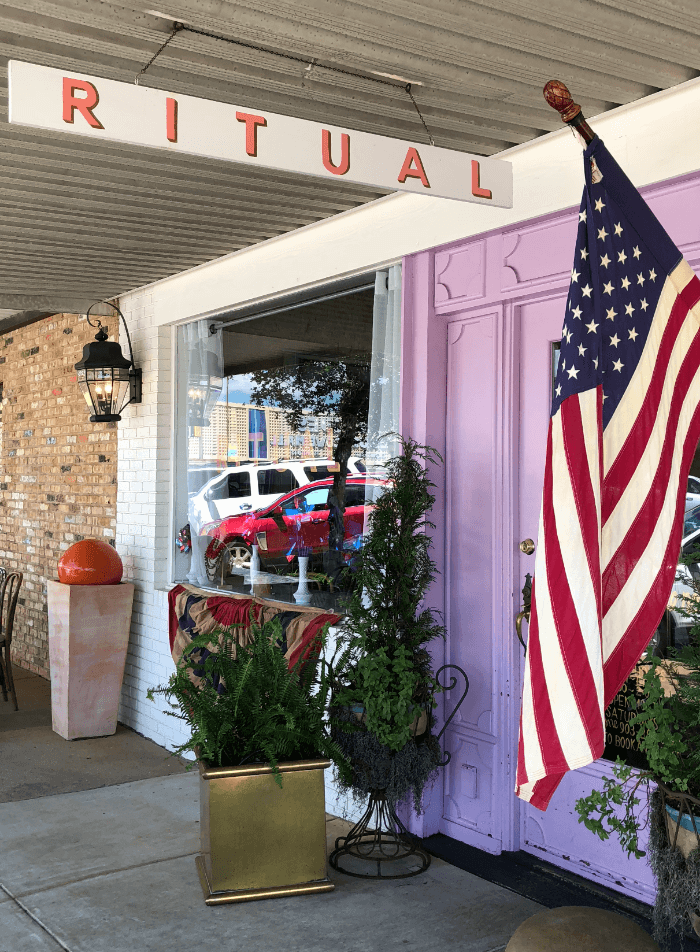 The pink front door of Ritual restaurant with an American Flag hanging on the wall