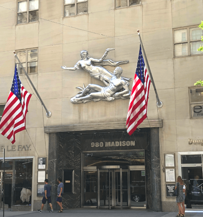 Exterior facade of 980 Madison Avenue with two American Flags