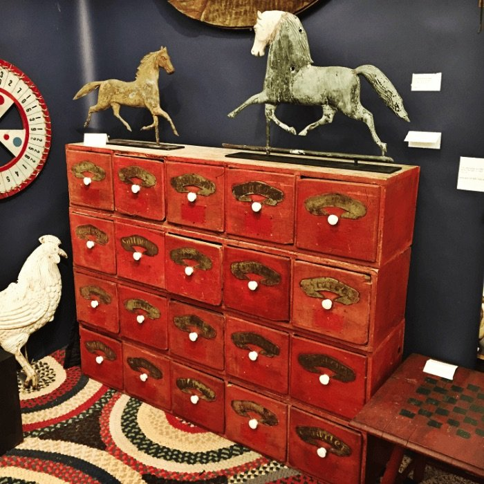 a red antique dresser with white knobs with two horse shaped weather vanes sitting on top