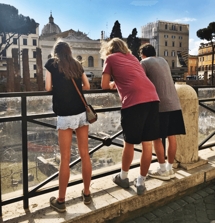 Three teenagers learning over a railing looking at ruins in Rome