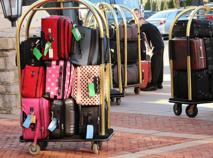 Stacks of Suitcases on rolling brass hotel luggage carts