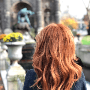 The back of a red haired woman who is standing in a garden with flowers and statues