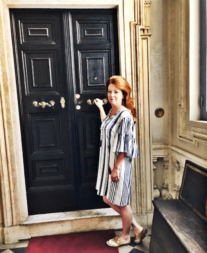 Woman with a blue and white dress opening an ornately carved black door