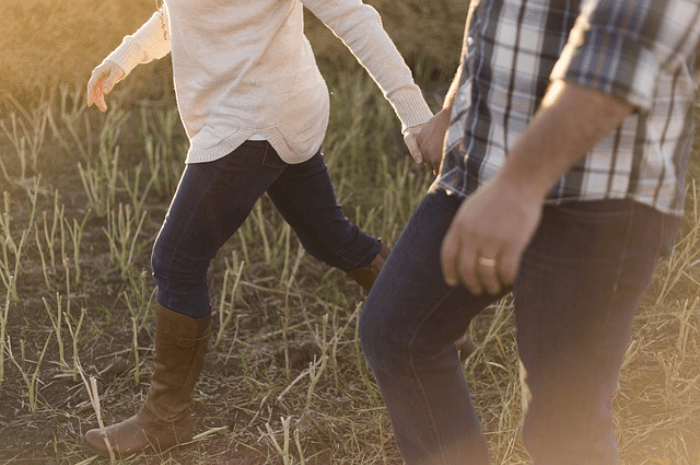 Man and woman holding hands and walking through tall grass